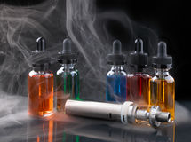 Electronic cigarette and vape liquids within vapor on black background Royalty Free Stock Images