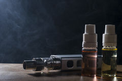Electronic cigarette, vaping device with e liquid background. Isolated e liquid drug and vaping device for electronic cigarette on a dark background stock image