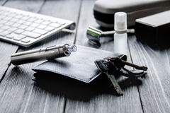 Electronic cigarettes and mens accessories on wooden background Royalty Free Stock Image