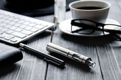 Electronic cigarettes and mens dark wooden desktop Royalty Free Stock Photos