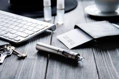 Electronic cigarettes and mens dark wooden desktop Stock Image