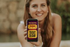 Happy blonde girl holding a mobile phone with digital cinema tickets in the screen. Electronic cinema tickets in a mobile phone screen Royalty Free Stock Photography