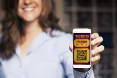 Smiling woman holding a mobile phone with digital cinema tickets in the screen. Electronic cinema tickets in a mobile phone screen Stock Photos