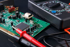 Electronic circuit board and digital multimeter Royalty Free Stock Photography