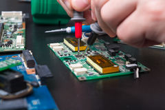 Electronic circuit board inspecting close up Royalty Free Stock Photo