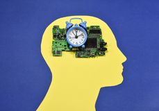 Small alarm clock and circuit board on male head contour. Electronic circuit board and small running alarm bell clock , placed on the yellow contour of a male Stock Photos