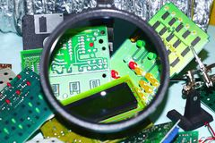 Electronic circuit boards on a blue background plus a magnifying glass. Electronic cards on a blue background shot through a round magnifying glass, well drawn stock photo