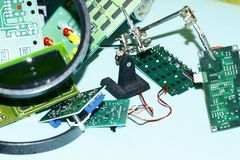 Electronic circuit boards on a blue background plus a magnifying glass. Electronic cards on a blue background shot through a round magnifying glass, well drawn stock images