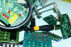 Electronic circuit boards on a blue background plus a magnifying glass. stock photography