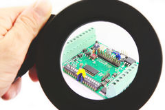 Electronic circuit with figure seen through magnifying glass. Royalty Free Stock Photography