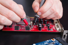 Electronic circuit red board inspecting close up Royalty Free Stock Photo