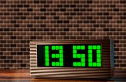 Electronic clock on the surface on a brick wall background stock image