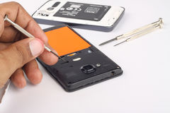 Electronic. Close-up of a man hand repairing a smartphone holding a micro screw driver Royalty Free Stock Photography