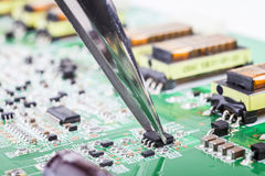 Electronic Component. Holding small electronic component with tweezer on green circuit board Royalty Free Stock Image
