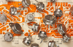 Electronic components. Old electronic components lie on the wiring diagram stock photography