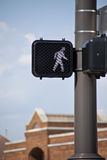 Electronic crosswalk sign surrounded by blue sky and brick build Stock Image