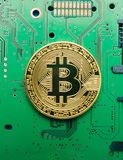 Electronic currency bitcoin on foul electrical circuits and boards.  royalty free stock photos