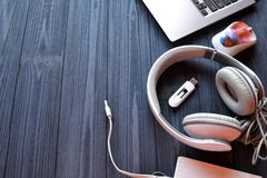 Electronic device on the workplace. Technology background. Laptop, mouse, headphones, usb and power bank on the dark blue wooden desk. Electronic device on the royalty free stock image