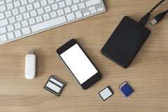 Electronic devices on a desk. An USB Stick an external hdd, different memory cards, a modern keyboard and a smartphone with white screen on a wooden desk stock image
