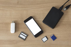 Electronic devices on a desk. An USB Stick an external hdd, different memory cards and a smartphone with white screen on a wooden desk stock photography