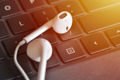 Electronic devices. Headphones on the keyboard. Online straming music service concept Stock Images