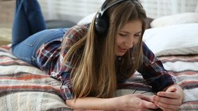 Electronic devices in the life of modern youth. young teenage girl resting at home on the bed with mobile phone. Electronic devices in the life of modern youth stock footage