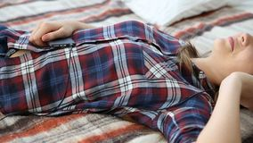 Electronic devices in the life of modern youth. young teenage girl resting at home on the bed with mobile phone. Electronic devices in the life of modern youth stock video footage