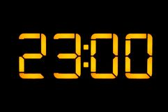 Electronic digital clock with orange numbers on a black background shows the time. Twenty three zero o`clock at night. Isolate, royalty free stock photos