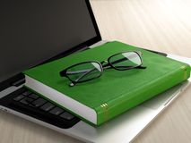 Electronic eduction. Laptop, green book and glasses on wooden desk. Electronic education concept Royalty Free Stock Images