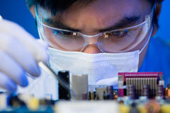 Electronic engineer at work. Close-up image of an engineer concentrated on electronic assembling on the foreground Stock Images