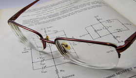 Electronic engineering book reading with glass on open page Royalty Free Stock Photos