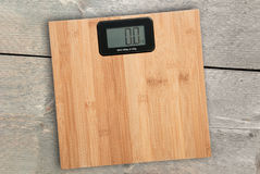 Electronic floor scale on a wooden background Stock Images