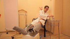 Electronic foot massage for man. Man phyto barrel electronic foot massage, tea ceremony stock video footage