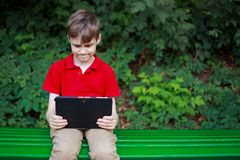 Electronic games addiction. Enthralled boy playing with tablet. stock photography