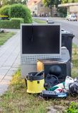 Electronic garbage on the roadside. Electronic garbage with a television, vacuum cleaner and other electrical appliances on the roadside stock photo