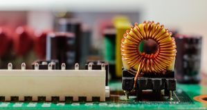 Electronic inductor on circuit board. Copper inductor component on electronic television board stock images