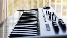 A keyboard instrument and its recording studio qualities. An electronic keyboard is set in a bright room. It has an 8 channel control board built in with faders royalty free stock photo