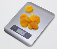 Electronic kitchen scale with dried apricots Royalty Free Stock Photos