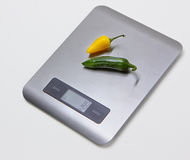 Electronic kitchen scales with peppers Stock Photography