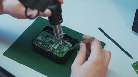 Electronic lab working place with soldering iron and circuit board. Electronics repair and fix service concept stock video footage