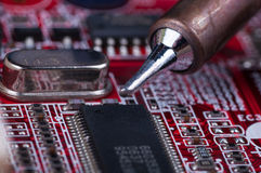 Electronic lab working place with soldering iron and circuit board Royalty Free Stock Image