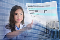Electronic medical record. Female doctor searching patient information from electronic medical record system royalty free stock photography