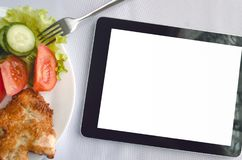 Electronic menu mock up. Food order online. Tablet computer with blank isolated screen and dish with fresh salad on the restaurant table background. Electronic Royalty Free Stock Photography