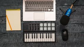 Electronic music mixer, laptop, pencil and wire microphone on a black wooden table. Equipment for the music Studio. The view from royalty free stock image