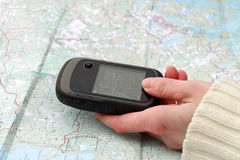 Electronic Navigator and Printed Map. Female hand is holding working navigator over the printed map royalty free stock photo
