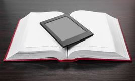 Electronic and paper books. On wooden background