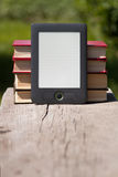 Electronic and paper books on wooden bench. Stock Photography