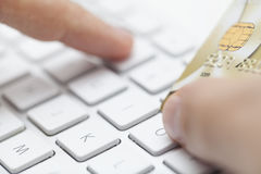 Electronic payment, transaction. Man is entering credit card number to computer Stock Image