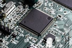 Electronic PCB Printed Circuit Board. In macro close-up with transistors circuitry and electric hardware elements including computer chip with copy space for Stock Images