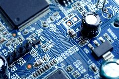 Electronic PCB Printed Circuit Board. In macro close-up with transistors circuitry and electric hardware elements including computer chip with copy space for Stock Image